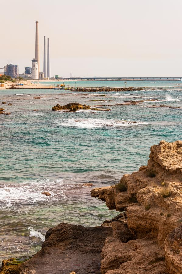 Rocce sulla spiaggia, sulle acque rocciose della costa di mar Mediterraneo e sul Orot Rabin, una centrale elettrica a carbone immagini stock libere da diritti