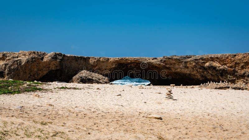 Rocce vicino ad una formazione di ponte naturale nella costa del nord del ` s di Aruba fotografie stock