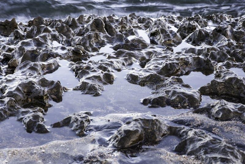 Rocce vulcaniche di luccichio su una spiaggia fotografia stock libera da diritti