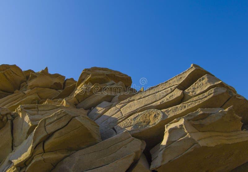 Roccia appuntita contro cielo blu fotografia stock libera da diritti