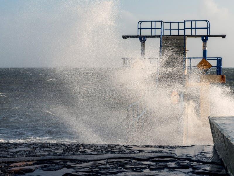 Roccia d'immersione di Black Rock alla tempesta e alta marea coperta da una spruzzata gigante di acqua Salthill, città di Galway, fotografie stock