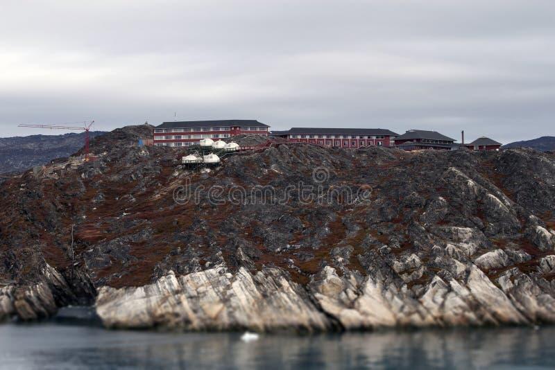 Roccia dell'hotel delle case del fiordo del fiordo della Groenlandia vicino alla gru a torre dell'oceano fotografia stock