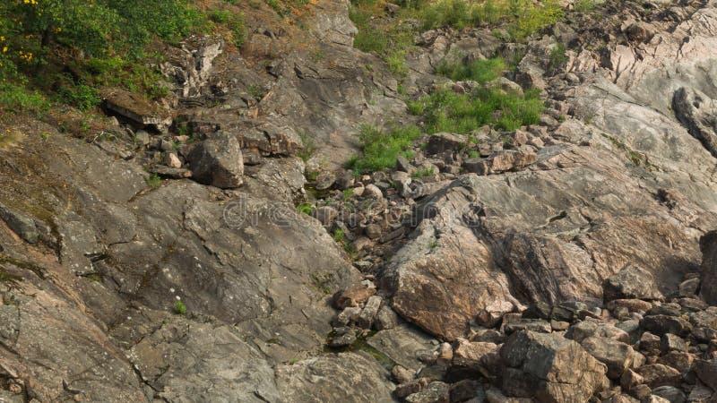 Roccia della pietra stratificata invasa con erba e muschio Struttura delle rocce di pietra fotografie stock