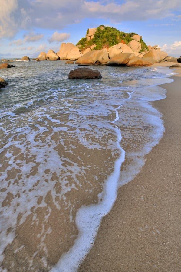 Roccia della spiaggia del mare nell ambito di illuminazione di tramonto