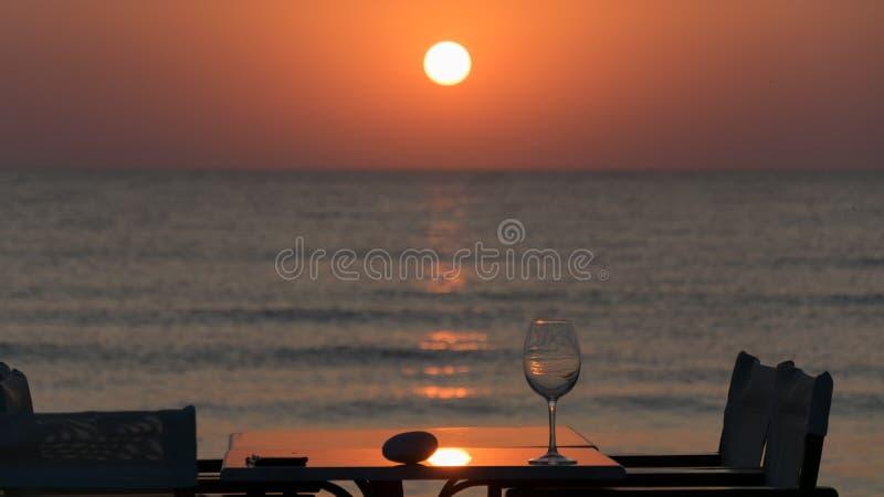 Roccia e vetro su una tavola con le sedie e sull'ombrello in canna, ad alba al mar Mediterraneo fotografia stock libera da diritti