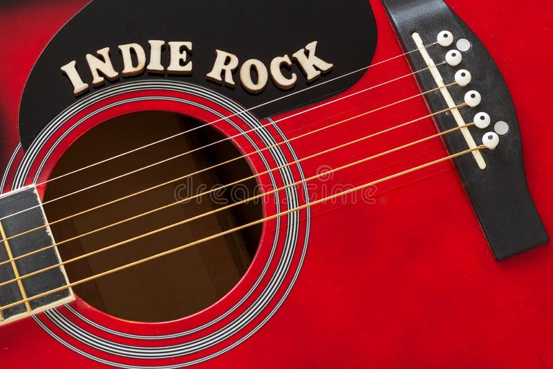 Roccia indipendente con le lettere di legno, primo piano di parole su una superficie della chitarra acustica rossa Fondo di spett fotografia stock libera da diritti