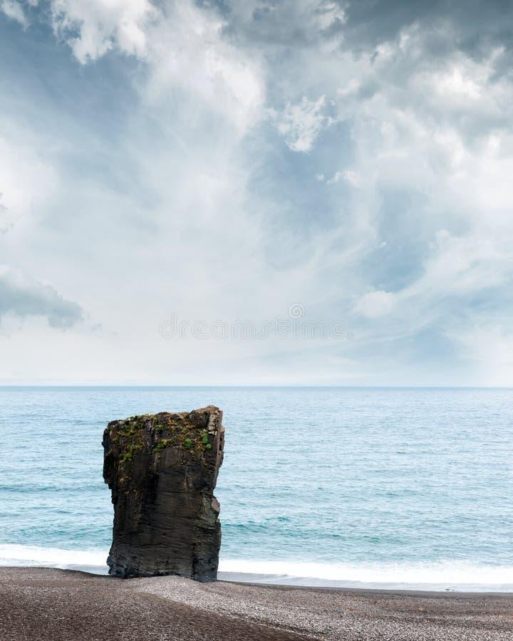 Roccia sola del basalto sulla linea costiera dell'Islanda fotografia stock
