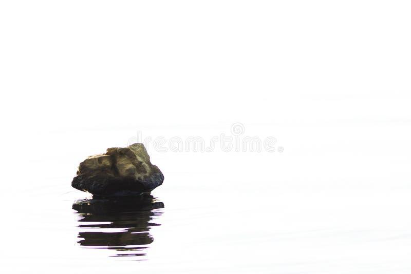 Roccia su acqua con la riflessione fotografie stock libere da diritti