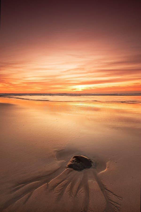 Roccia sulla spiaggia al tramonto fotografie stock libere da diritti