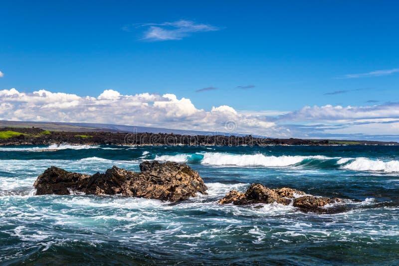 Roccia vulcanica, oceano e spuma; Spiaggia di sabbia del nero di Punaluu in Hawai Nuvole e cielo nel fondo; litorale nella distan fotografia stock