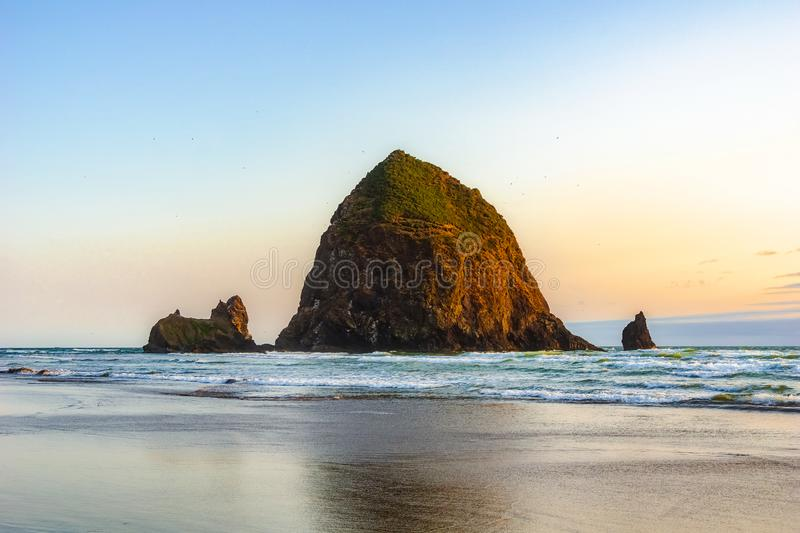 Rocha bonita do monte de feno, marco natural famoso da Costa do Pacífico, no por do sol, praia do canhão, costa de Oregon fotos de stock