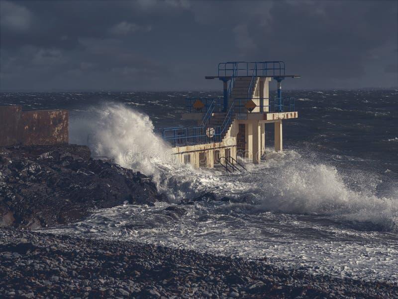 Rocha de mergulho de Black Rock na tempestade e maré alta coberta por um respingo gigante da água Salthill, cidade de Galway, Irl fotografia de stock
