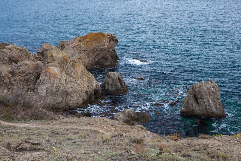 Rocha de pedra grande sobre a água do mar imagem de stock