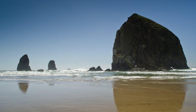 Rocha do monte de feno na praia do canhão em Oregon fotografia de stock