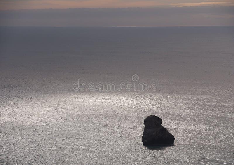 Rocha e projetor a pouca distância do mar imagem de stock