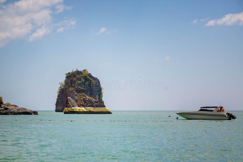 A rocha no mar de andaman é pintada com pintura do ouro Espiritualidade tailandesa Flutuadores da lancha pr?ximo C?u azul, muitas imagens de stock