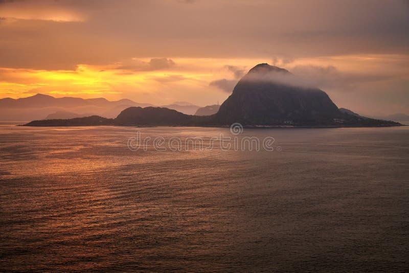 Rocha no oceano com as nuvens no nascer do sol foto de stock royalty free