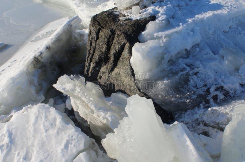 Rocha que estoura através do gelo, mar Báltico congelado, Helsínquia, Finlandia foto de stock