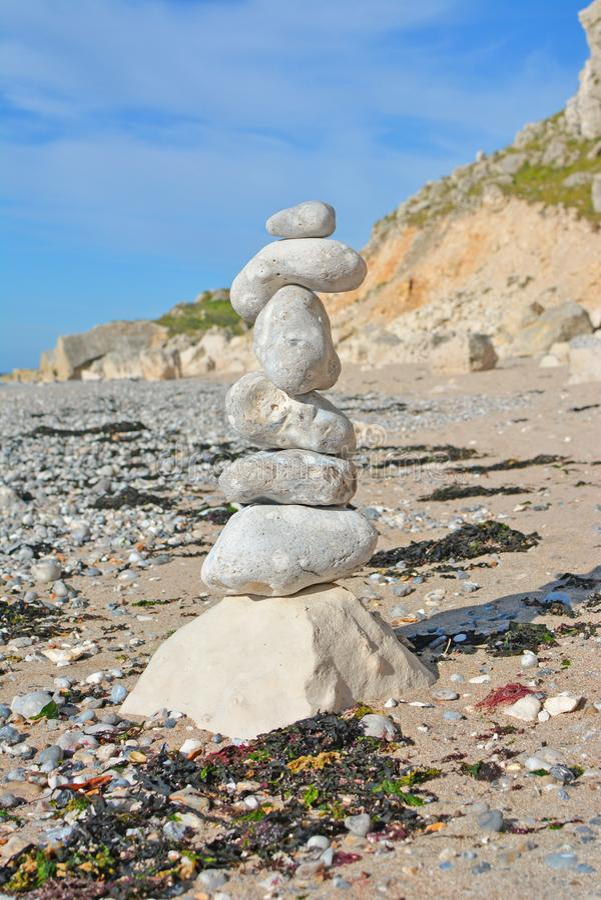 Rocha simples que equilibra com as pedras brancas na praia na frente do céu azul foto de stock