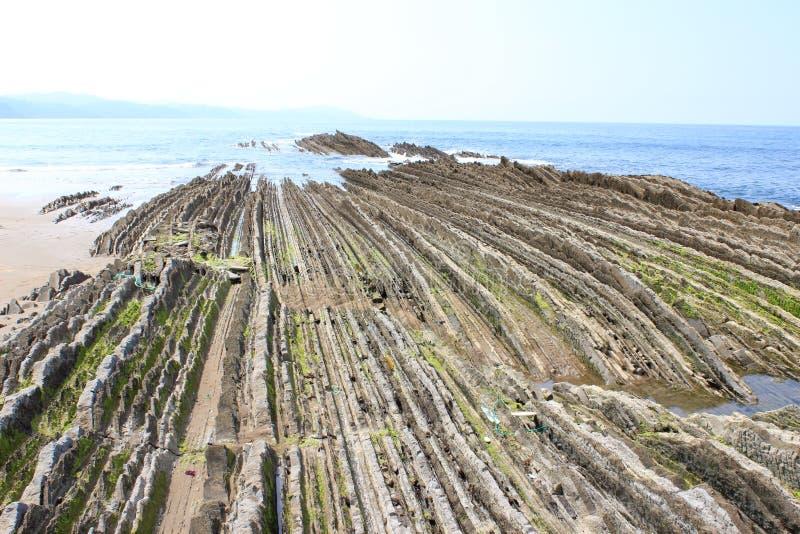 Rochas afiadas na praia sob o sol imagens de stock royalty free