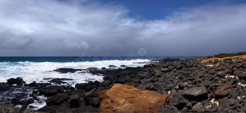 Rochas alaranjadas e pretas na costa do oceano foto de stock royalty free
