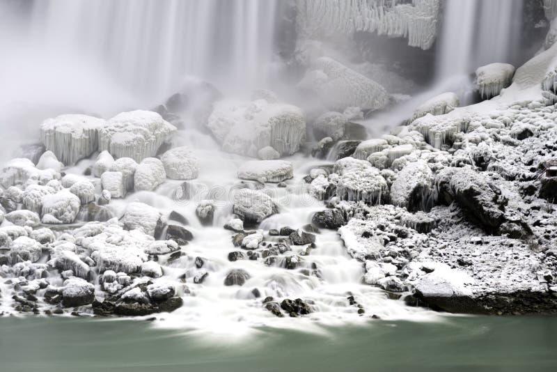 Rochas cobertos de neve sob a grande cachoeira que flui no aqu liso fotos de stock royalty free