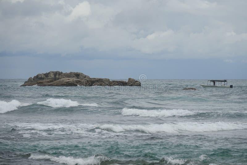 Rochas com um barco de pesca no oceano foto de stock royalty free