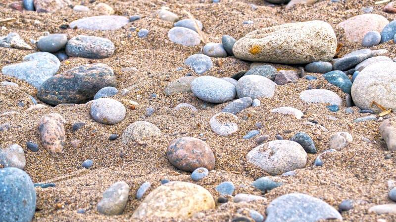 Rochas da areia, do vermelho, do cinza, as amarelas e as azuis na costa do lago fotografia de stock