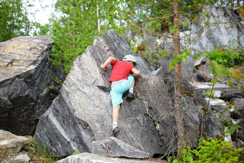 Rochas de escalada do menino caucasiano novo da criança na floresta imagem de stock royalty free