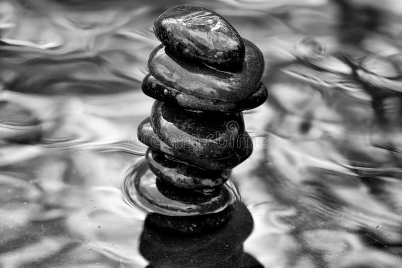 Rochas do zen do ` do empilhador do ` empilhadas na água com despesas gerais dos membros de árvore imagens de stock