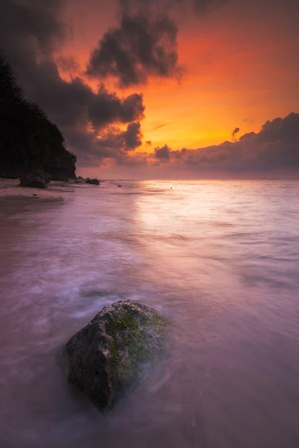 Rochas e musgo verde no nascer do sol em uma praia imagens de stock royalty free