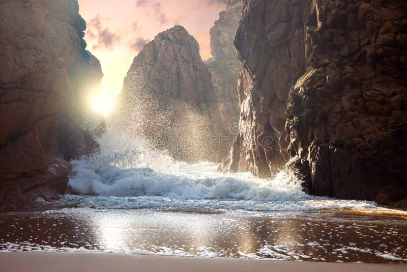 Rochas e ondas de oceano grandes no pôr do sol imagem de stock royalty free