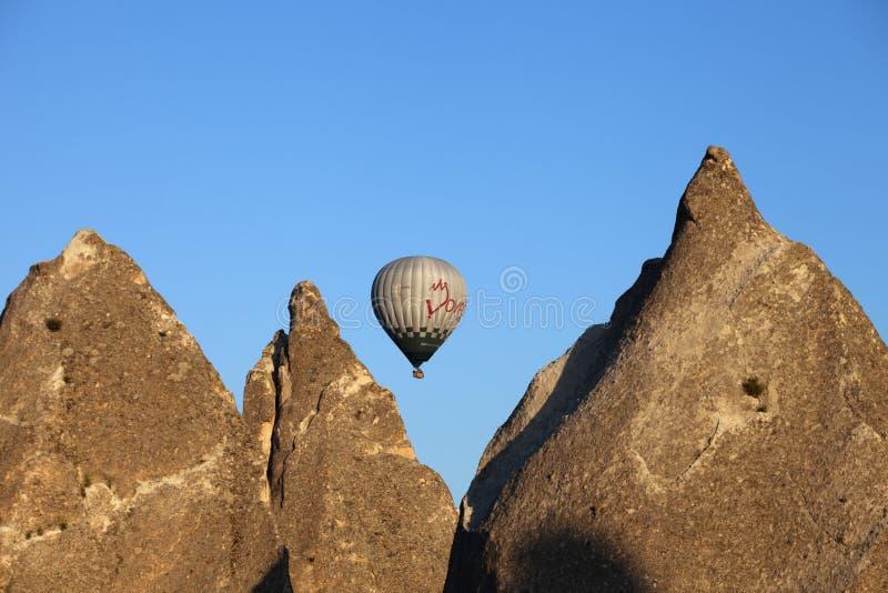 Rochas ensolarados e balão de ar quente no céu azul claro foto de stock