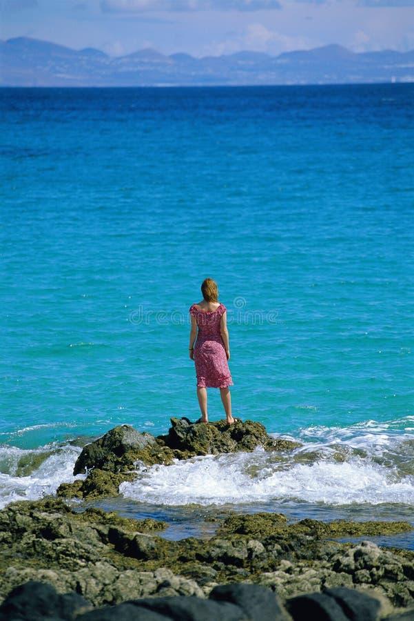 Rochas eretas da mulher nova, olhando para fora ao mar imagem de stock royalty free