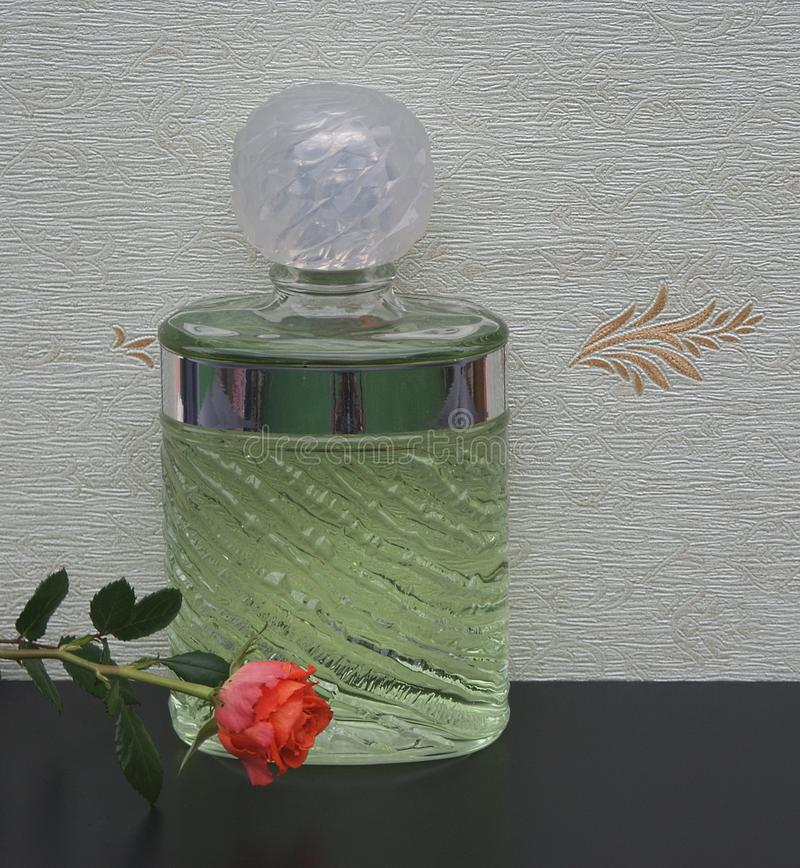 Eau de Rochas, fragrance for ladies, large perfume bottle in front of the satin wallcovering Elysee decorated with an English rose royalty free stock images