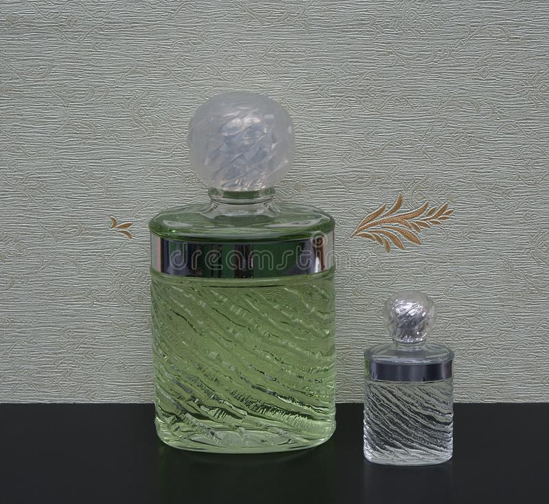 Eau de Rochas, fragrance for ladies, large perfume bottle next to a commercial perfume bottle in front of the satin wallcovering royalty free stock photography