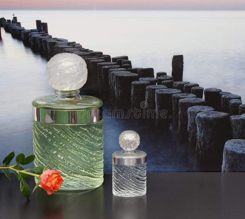Eau de Rochas, fragrance for ladies, large perfume bottle next to a commercial perfume bottle in front of the picture of a groyne royalty free stock photo