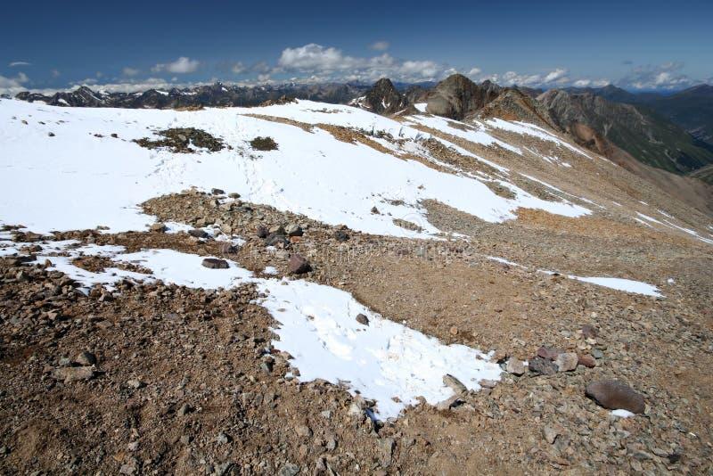 Rochas, neve, céu e nuvens nas montanhas imagem de stock