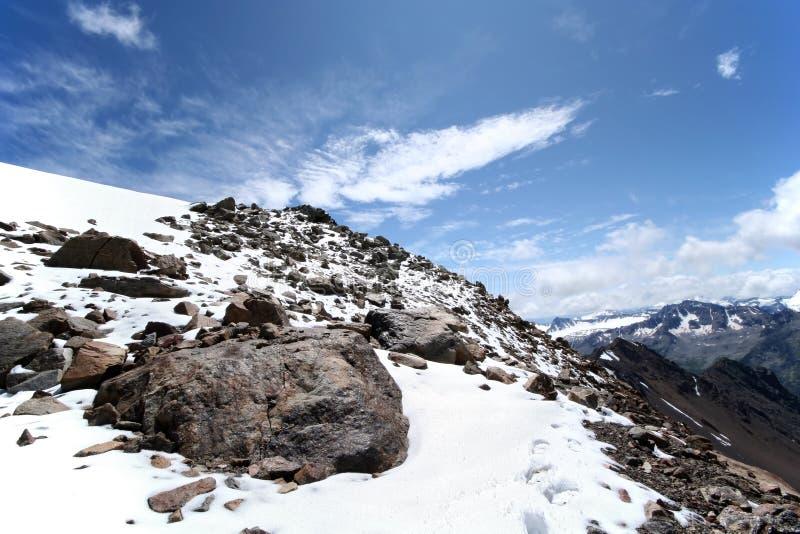 Rochas, neve, céu e nuvens nas montanhas fotografia de stock