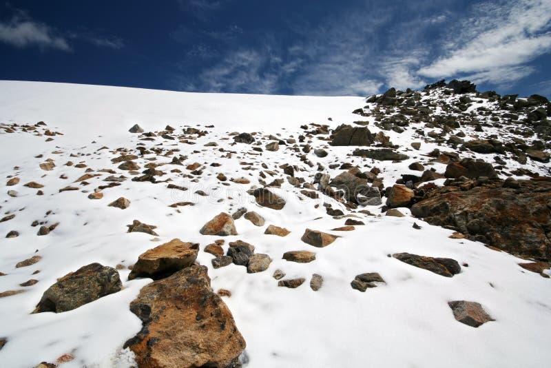 Rochas, neve, céu e nuvens nas montanhas fotos de stock