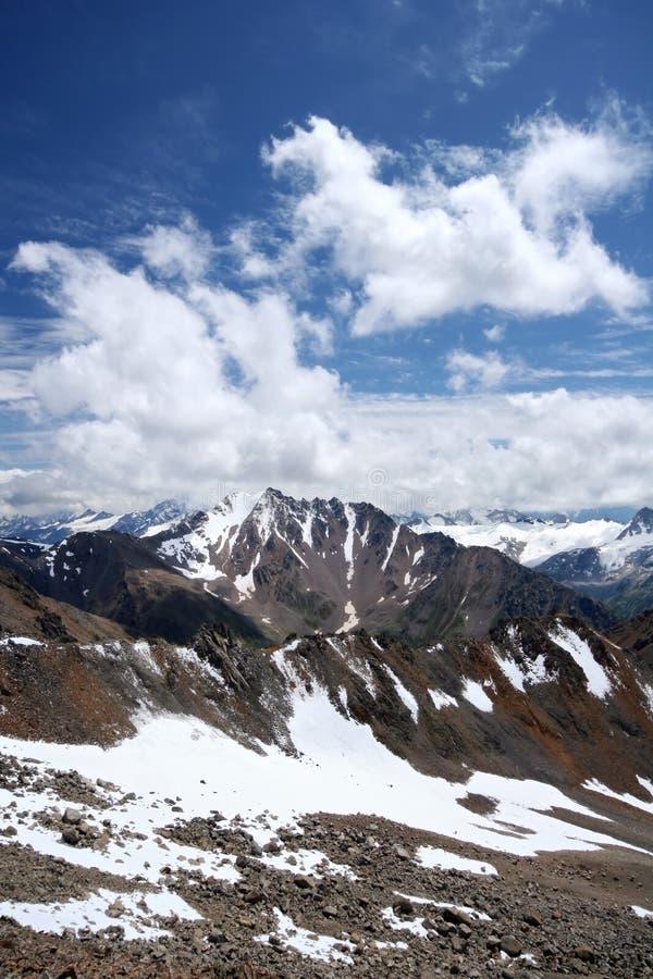 Rochas, neve, nuvens e céu em montanhas de Cáucaso imagem de stock royalty free