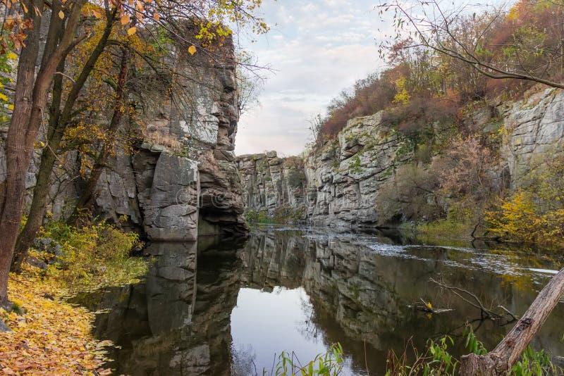 Rochas pendendo sobre sobre o rio calmo na garganta no outono atrasado imagens de stock