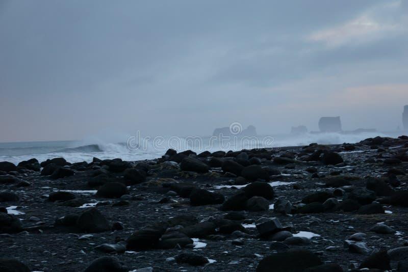 Rochas pretas com as ondas despedaçando-se no fundo na praia de Reynisfjara em Islândia imagens de stock