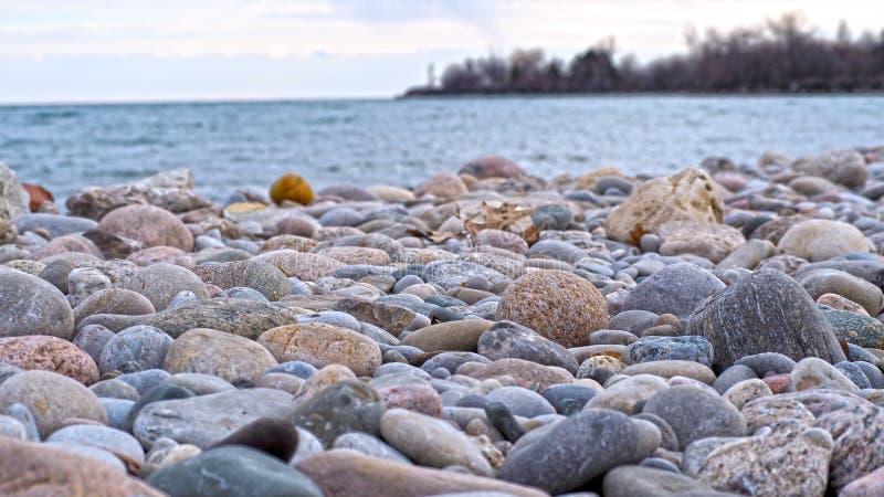 Rochas vermelhas, cinzentas, amarelas e azuis na costa do lago fotografia de stock