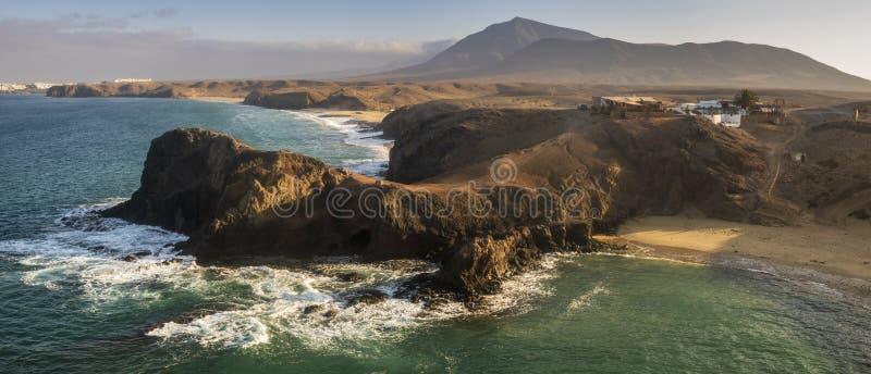 Rochas vulcânicas no oceano na praia de Papagayo durante o nascer do sol imagem de stock royalty free