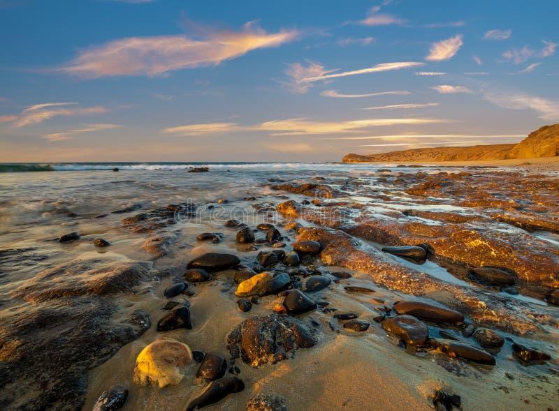 Rochas vulcânicas no oceano na praia de Papagayo em Lanzarote durante o nascer do sol imagem de stock royalty free