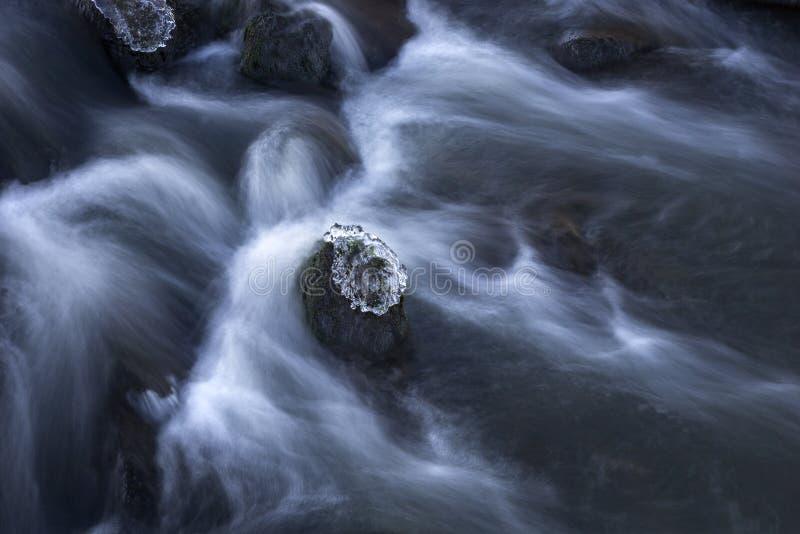 Roche avec de la glace en coulant l'eau photo stock