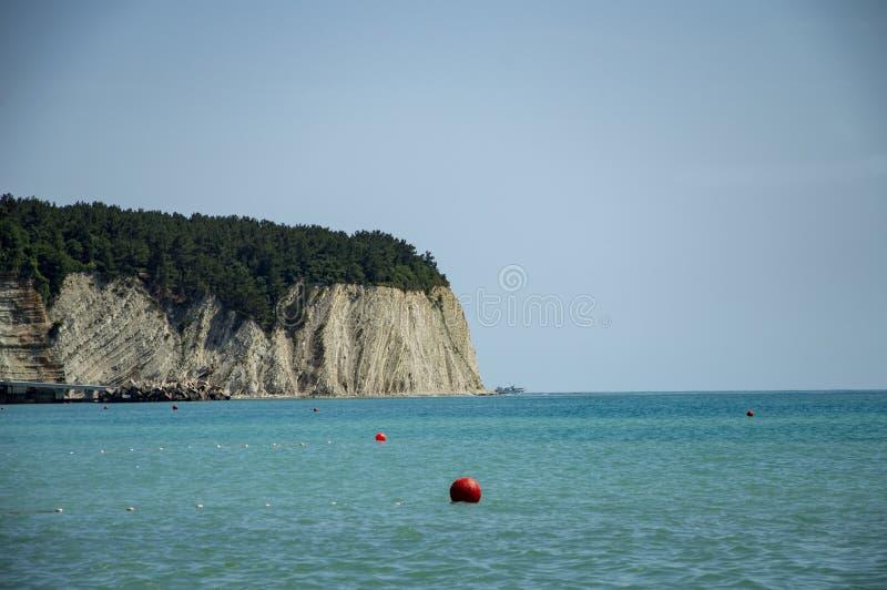 Roche contre la mer et le ciel bleu photo stock
