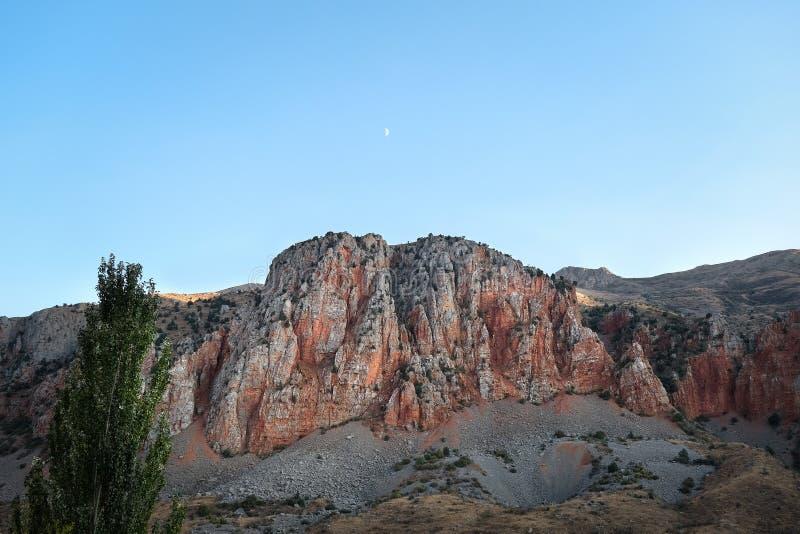 Roche en pierre rouge contre un ciel bleu clair photographie stock