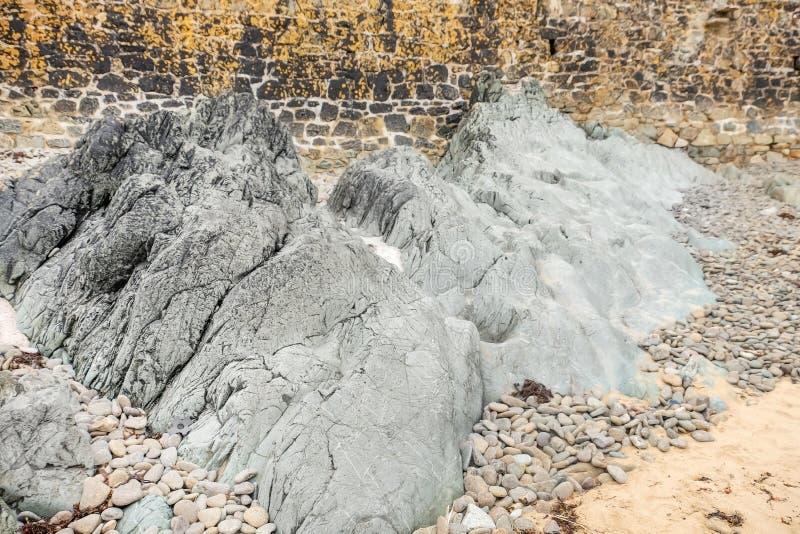 Roche et cailloux sur la plage sablonneuse photos libres de droits